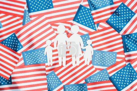 Photo pour Vue supérieure de la famille coupée de papier blanc sur le fond américain de drapeaux - image libre de droit