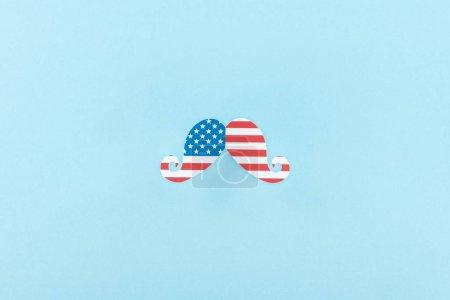 Photo pour Vue supérieure de la moustache décorative coupée en papier faite du drapeau américain sur le fond bleu - image libre de droit
