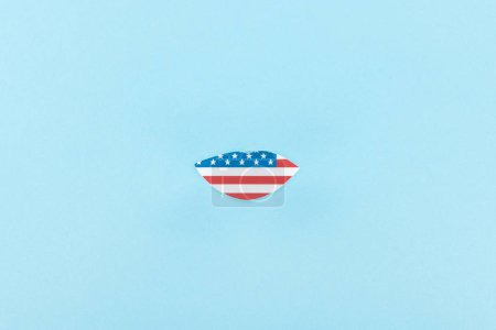 Photo for Top view of paper cut decorative lips made of american flag on blue background - Royalty Free Image