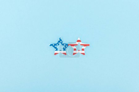 Photo for Top view of paper cut decorative glasses made of american flag on blue background - Royalty Free Image
