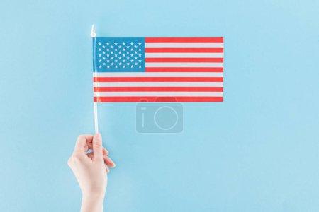 Photo pour Vue recadrée de femme retenant le drapeau américain national sur le bâton sur le fond bleu - image libre de droit