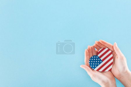 Photo pour Cropped view of woman holding heart made of national american flag on blue background with copy space - image libre de droit