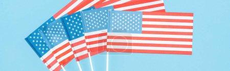 Photo pour Tir panoramique des drapeaux américains sur des bâtons sur le fond bleu - image libre de droit
