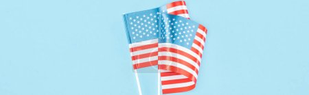 Photo pour Panoramic shot of usa flags on sticks on blue background - image libre de droit
