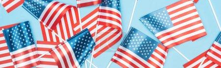 Photo pour Tir panoramique de drapeaux américains dispersés sur des bâtons sur le fond bleu - image libre de droit