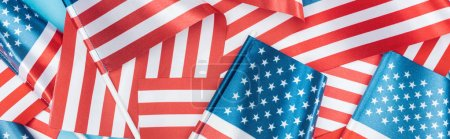 Photo pour Panoramic shot of american flags stacked on blue background - image libre de droit