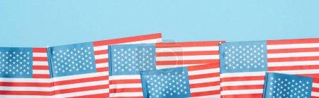 Photo pour Tir panoramique des drapeaux américains patriotiques nationaux sur le fond bleu - image libre de droit