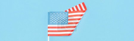 Photo for Top view of american flag on stick on blue background, panoramic shot - Royalty Free Image