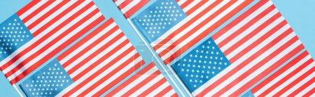 Photo pour Plat s'est couché avec des drapeaux américains sur des bâtons sur le fond bleu, projectile panoramique - image libre de droit