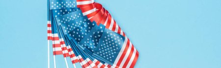 Foto de Panoramic shot of glossy american flags on sticks on blue background - Imagen libre de derechos