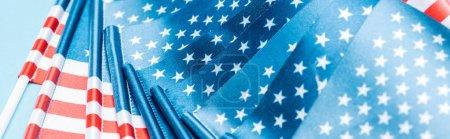 Photo pour Fermer vers le haut la vue des drapeaux américains brillants sur le fond bleu, projectile panoramique - image libre de droit