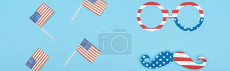 Photo pour Plan panoramique de lunettes et de moustache fait d'étoiles et de rayures près de drapeaux américains décoratifs sur bâtons de bois sur fond bleu - image libre de droit