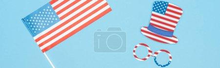Foto de Foto panorámica de gafas y sombrero hecho de estrellas y rayas cerca de la bandera americana en el fondo azul - Imagen libre de derechos