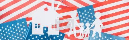 Photo pour Prise de vue panoramique de la maison en papier blanc coupé et la famille sur fond de drapeaux américains - image libre de droit