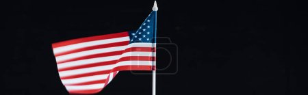 panoramic shot of national american flag on stick isolated on black with copy space