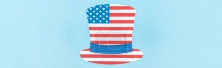 Photo pour Vue supérieure du chapeau décoratif coupé en papier fait du drapeau américain sur le fond bleu, projectile panoramique - image libre de droit