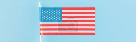 top view of decorative american flag on stick on blue background, panoramic shot