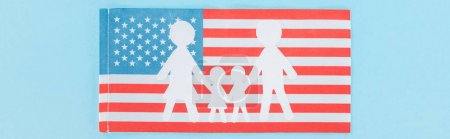 Photo for Panoramic shot of paper cut white family on national american flag on blue background - Royalty Free Image