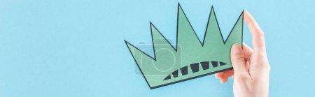 Photo pour Tir panoramique de femme retenant la couronne coupée de papier sur le fond bleu avec l'espace de copie, concept de jour d'indépendance - image libre de droit