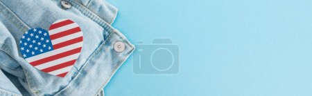 top view of paper cut heart made of american flag on denim stylish jacket on blue background with copy space, panoramic shot