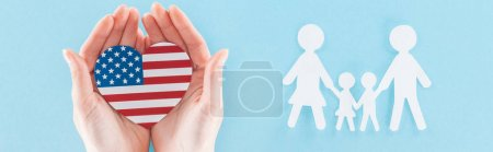 panoramic shot of woman holding heart made of national american flag near white paper cut family on blue background