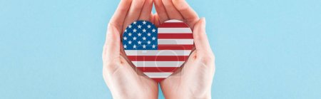 panoramic shot of woman holding heart made of american flag on blue background with copy space