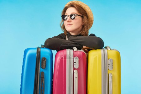 Photo pour Fille souriante dans des lunettes de soleil et chapeau de paille près de sacs de voyage multicolores isolés sur bleu - image libre de droit