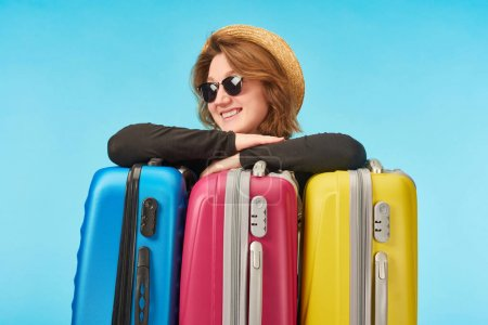 Photo for Happy girl in sunglasses and straw hat near multicolored travel bags isolated on blue - Royalty Free Image