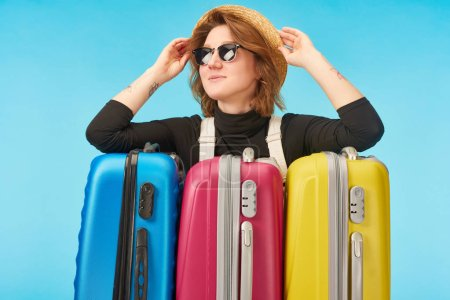 Photo pour Fille gaie dans des lunettes de soleil et chapeau de paille près de sacs de voyage multicolores isolés sur bleu - image libre de droit