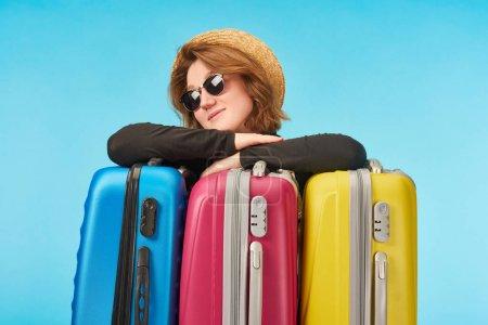 Photo pour Fille positive dans des lunettes de soleil et chapeau de paille près de sacs de voyage multicolores isolés sur bleu - image libre de droit