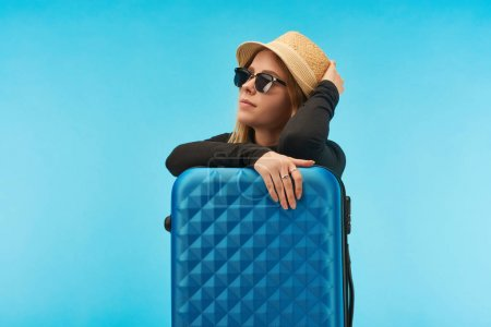 Photo for Blonde girl in sunglasses and straw hat near blue suitcase isolated on blue - Royalty Free Image