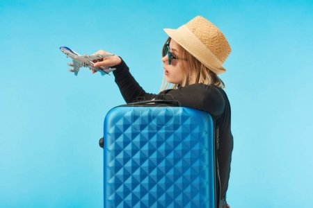 Photo for Blonde girl in sunglasses and straw hat playing with toy airplane near blue travel bag isolated on blue - Royalty Free Image