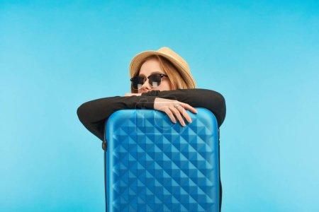 Photo pour Blonde fille en lunettes de soleil et chapeau de paille près sac de voyage bleu isolé sur bleu - image libre de droit