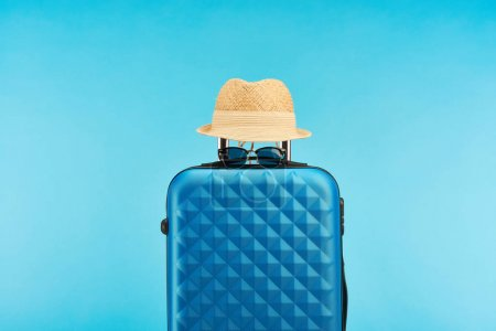 Photo for Blue colorful travel bag with sunglasses and straw hat isolated on blue - Royalty Free Image