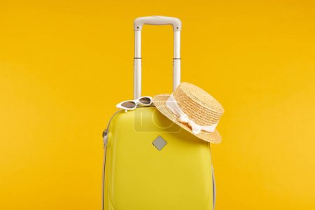 Photo pour Yellow colorful travel bag with sunglasses and straw hat isolated on yellow - image libre de droit