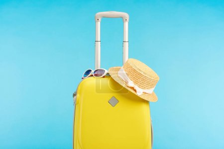 Photo for Yellow colorful travel bag with straw hat and sunglasses isolated on blue - Royalty Free Image