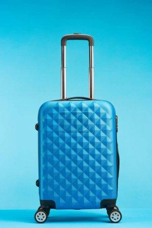 Foto de Bolsa de viaje azul con asa sobre ruedas sobre fondo azul - Imagen libre de derechos