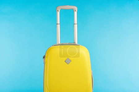 Photo for Yellow colorful travel bag with handle isolated on blue - Royalty Free Image