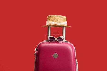 Photo pour Sac de voyage coloré rouge avec chapeau de paille et lunettes de soleil isolées sur rouge - image libre de droit