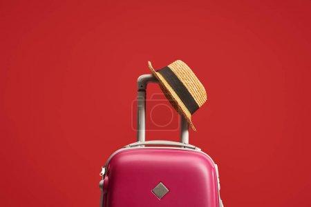 Photo pour Sac de voyage coloré avec chapeau de paille isolé sur rouge - image libre de droit