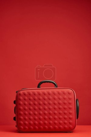 red colorful textured travel bag isolated on red with copy space