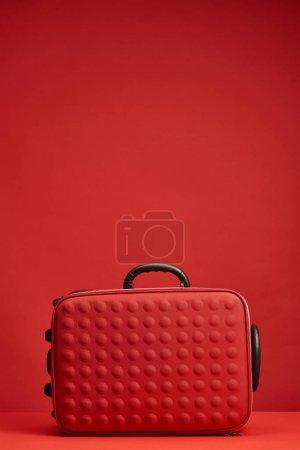 Photo pour Sac de voyage texturé coloré rouge isolé sur rouge avec espace de copie - image libre de droit