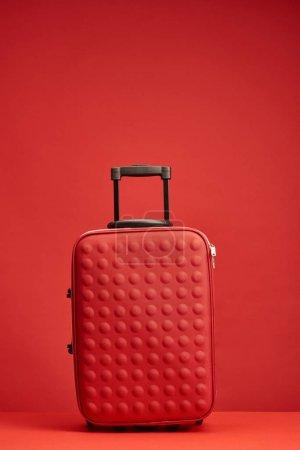 Photo pour Sac de voyage texturé coloré rouge isolé sur rouge - image libre de droit