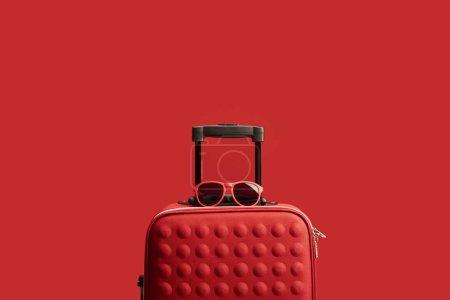 Photo pour Sac de voyage texturé coloré rouge avec des lunettes de soleil isolées sur rouge - image libre de droit
