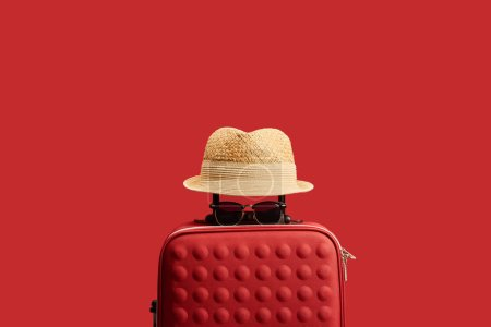 red travel bag with straw hat and sunglasses isolated on red