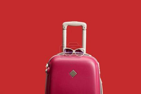 Foto de Bolsa de viaje roja colorida con gafas de sol aisladas en rojo - Imagen libre de derechos