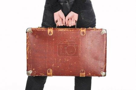 Photo pour Vue partielle de femme dans des jeans retenant la valise en cuir de cru d'isolement sur le blanc - image libre de droit