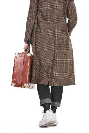 Photo pour Vue arrière de la femme dans le manteau à carreaux retenant la valise altérée de cru d'isolement sur le blanc - image libre de droit