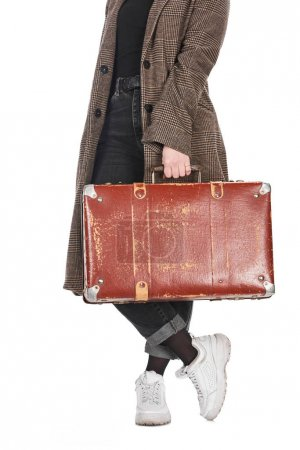 Photo for Cropped view of woman in plaid coat with crossed legs holding vintage weathered suitcase isolated on white - Royalty Free Image