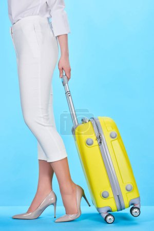 Photo pour Vue recadrée de la femme tenant poignée de sac de voyage jaune sur fond bleu - image libre de droit